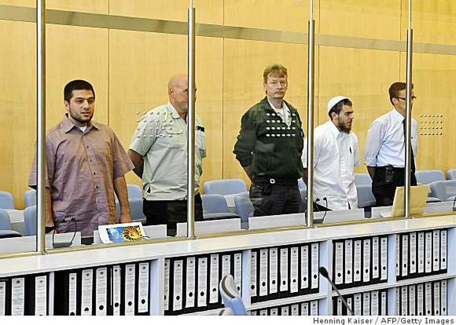 CAPTION CORRECTION - Corrects defendant's name German defendant Daniel Schneider (2nd R) and German defendant of Turkish origin Atilla Selek (L) stand inside the high-security courtroom of the superior regional tribunal in the western city of Duesseldorf, on June 9, 2009 during one of Germany's biggest terror trials in decades against four alleged Islamic extremists, three Germans and a Turkish national, accused of plotting devastating attacks against US interests. Media reports said the Four suspected Islamic militants were planning to confess to playing a role in a plan to attack US targets in Germany in 2007.       AFP PHOTO    DDP / HENNING KAISER    GERMANY OUT (Photo credit should read HENNING KAISER/AFP/Getty Images) Photo: Henning Kaiser, AFP/Getty Images