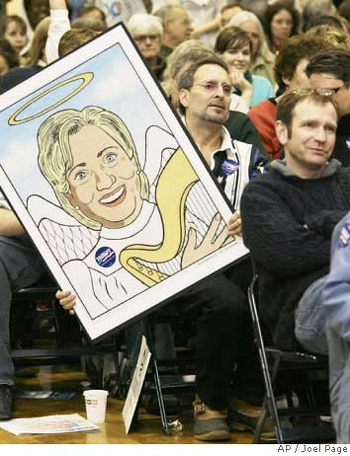 Doug Emerson holds a poster depicting Democratic presidential hopeful Sen. Hillary Clinton Sunday, Feb. 10, 2008, during the Democratic Caucus at Portland High School in Portland, Maine. (AP Photo/Joel Page)