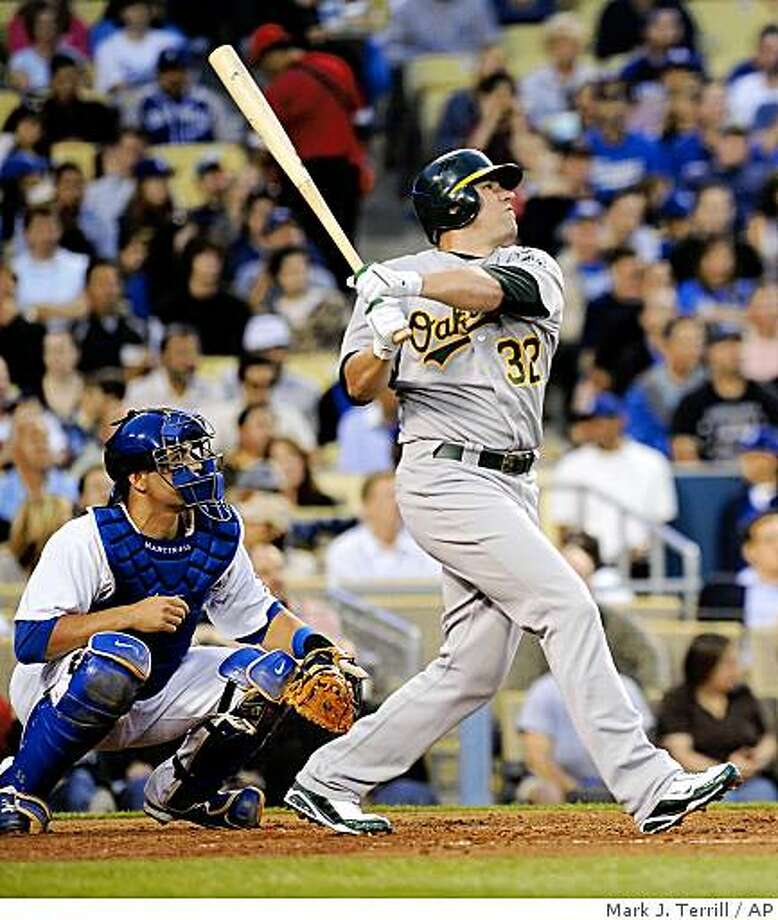 Oakland Athletics' Jack Cust, right, hits a two-run home run as Los Angeles Dodgers catcher Russell Martin looks on during the third inning the A's 5-4 win over the Dodgers on Wednesday night. Photo: Mark J. Terrill, AP