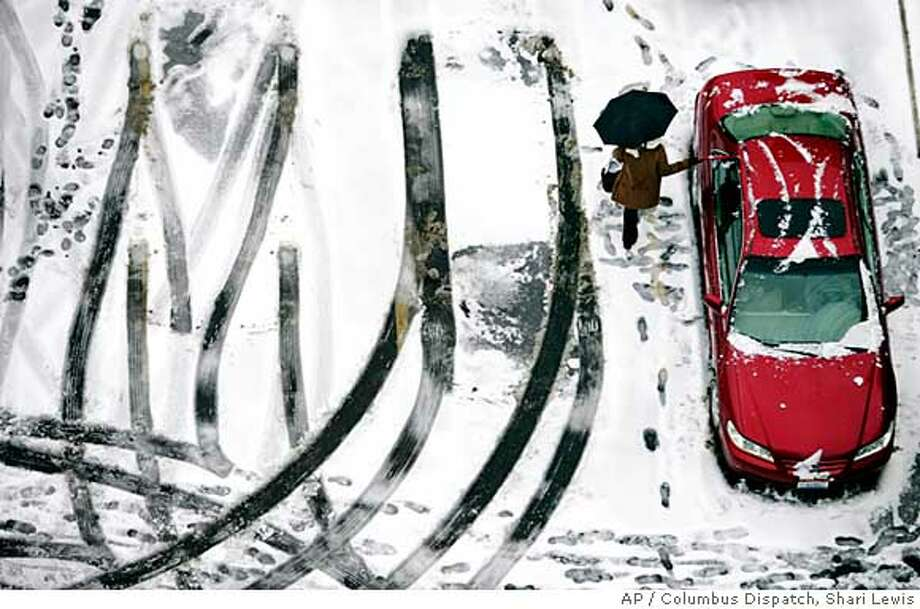A driver clears snow off her car at the end of the work day in a downtown Columbus, Ohio, parking lot Tuesday, Feb. 12, 2008. (AP Photo/Columbus Dispatch, Shari Lewis) Photo: Shari Lewis
