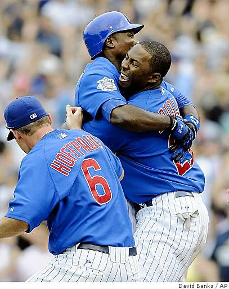 Chicago Cubs' Alfonso Soriano gets a hug from Milton Bradley, right, after Soriano's game-winning hit during the ninth inning of an interleague baseball game against the Chicago White Sox on Thursday, June 18, 2009,  at Wrigley Field in Chicago. The Cubs won 6-5. At left is Micah Hoffpauir. (AP Photo/David Banks) Photo: David Banks, AP