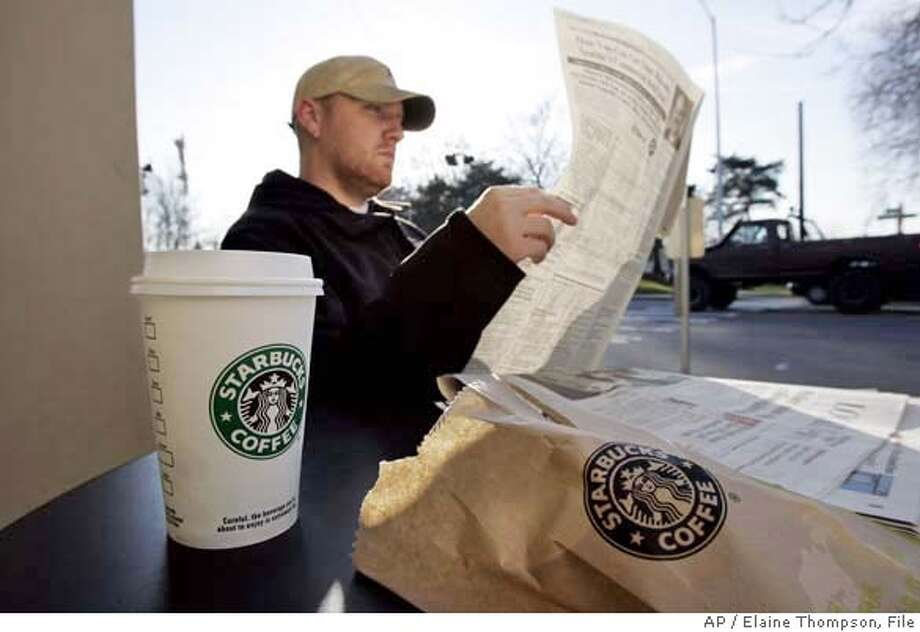 ** FILE ** J.J. Geise reads a paper as he treats himself to coffee and a baked good at a Starbucks coffee shop in Seattle in this Jan. 25, 2008 file photo. Starbucks Corp. is teaming up with AT&T Inc. and will start offering a mix of free and paid wireless Internet service in many of its U.S. coffee shops, beginning this spring. (AP Photo/Elaine Thompson, file) JAN 25, 2008 FILE PHOTO Photo: Elaine Thompson