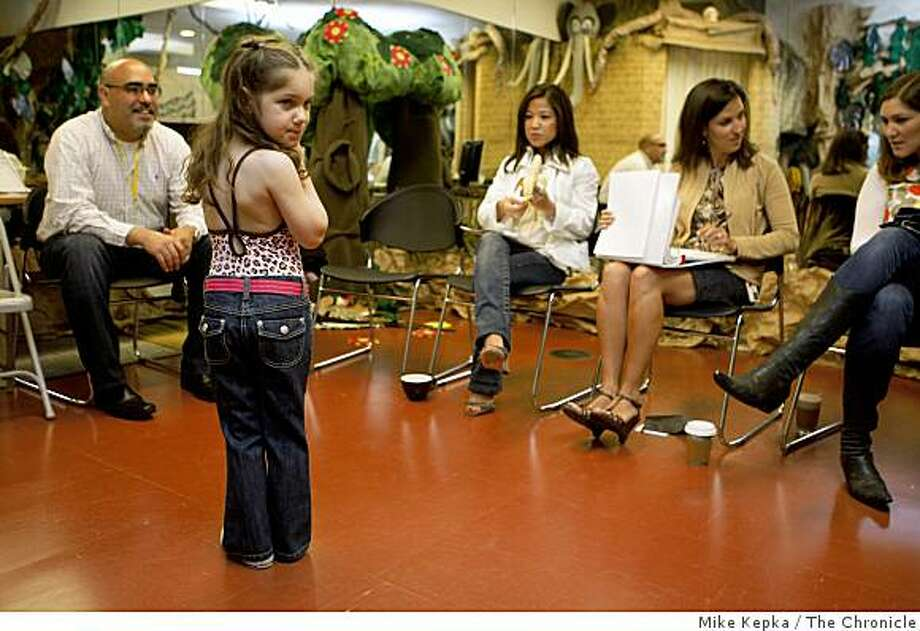 As Dad watches on the left, Gymboree designers look over next season's line while Lily Figueroa, 4, with Marla Dell modeling agency stands in for a live model fitting at Gymboree Headquartes on Wednesday May 28, 2009 in San Francisco, Calif. Photo: Mike Kepka, The Chronicle