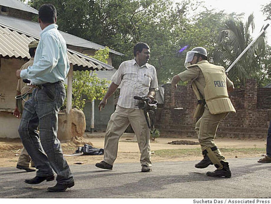 A policeman beats a member of the media at Pirakata, in west Midnapore, about 145 kilometers (91 miles) west of Calcutta, India, Thursday, June 18, 2009. Authorities sent hundreds of soldiers Thursday to a remote area of eastern India where Maoist rebels captured more than a dozen villages, killed political rivals and burned police stations and government offices, police said. Police said troops sent had met resistance, mainly from the local population who had felled trees to block roads leading to the area, in support of the Maoists. The rebels, who say they are inspired by Chinese revolutionary leader Mao Zedong, have been fighting for more than three decades in several Indian states, demanding land and jobs for agricultural laborers and the poor. Photo: Sucheta Das, Associated Press