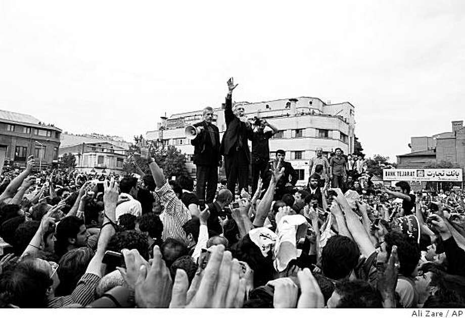 Iranian opposition leader Mir Hossein Mousavi, center, speaks to  supporters at a demonstration in Tehran on Thursday June, 18, 2009.  Tens of thousands of black-clad protesters filled the streets of Tehran again Thursday, joining opposition leader Mir Hossein Mousavi to mourn demonstrators killed in clashes over Iran's disputed election. Photo: Ali Zare, AP