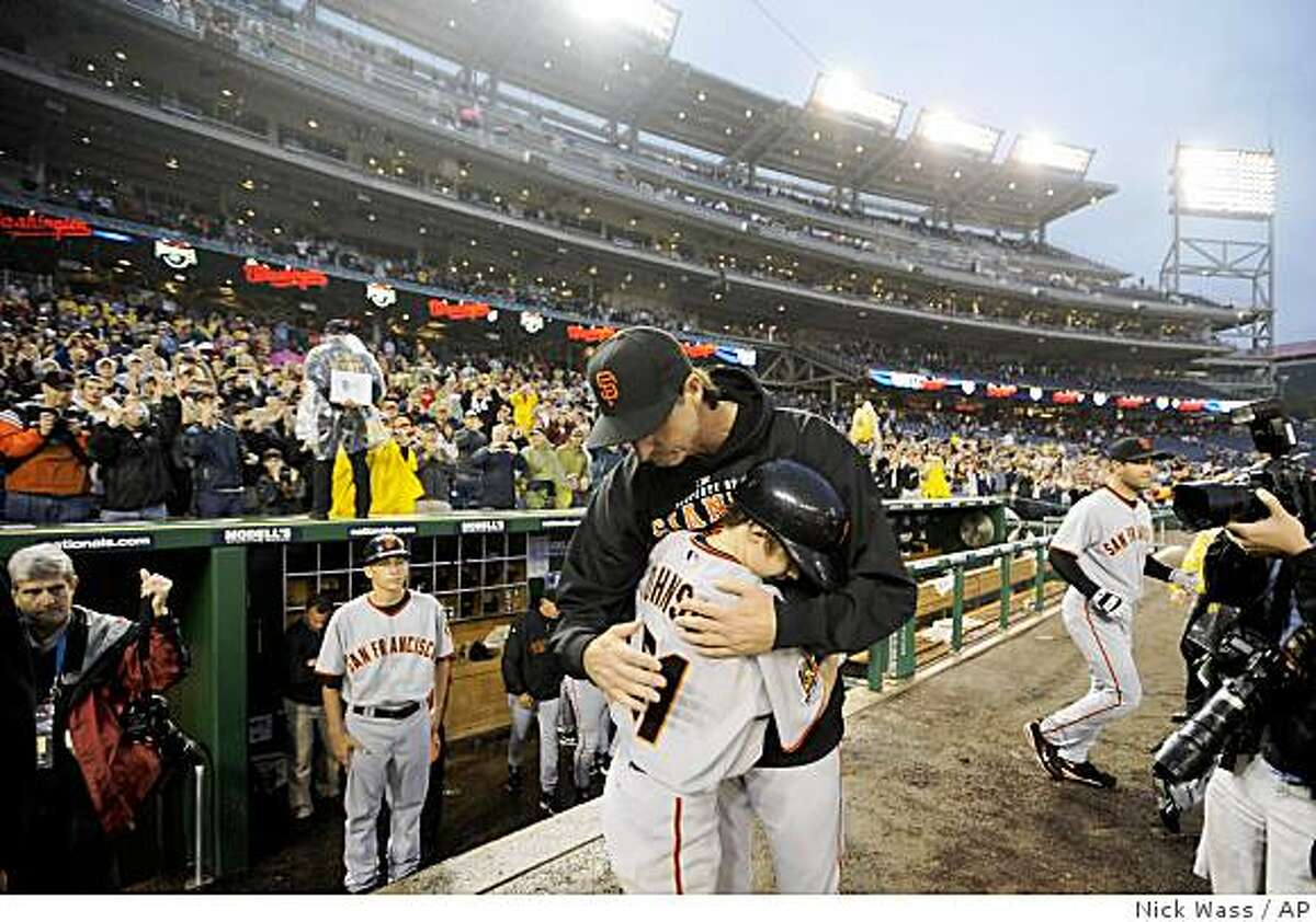 San Francisco Giants starting pitcher Randy Johnson hugs his son Tanner after the Giants beat the Washington Nationals 5-1 for Johnson's 300th career win.