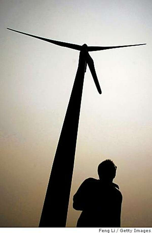NANTONG, CHINA - JUNE 02:  A man walks under a wind power generator at Rudong wind farm on June 2, 2009 in Nantong of Jiangsu Province, China. China started to build national oil reserve bases as early as in 2003 to offset oil supply risks and reduce the impact of fluctuating energy prices. China's top economic planning agency will soon submit a draft support plan of the country's new energy industry to the State Council for approval, a plan that would focus on nuclear power and renewable energy as wind and solar power, according to an official of the National Bureau of Energy.  (Photo by Feng Li/Getty Images) Photo: Feng Li, Getty Images