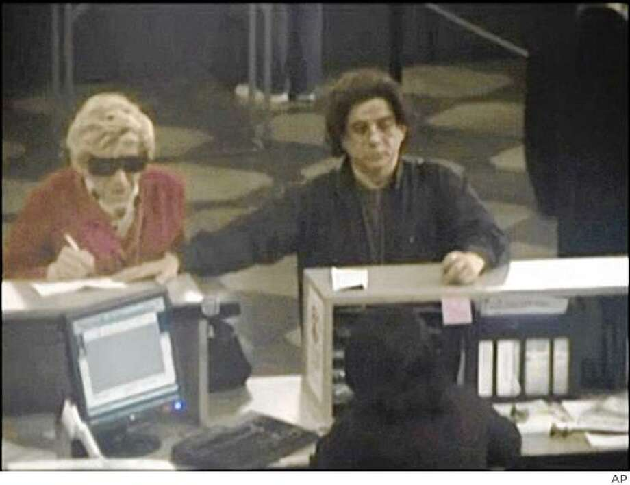 This May 2009 image provided by the Brooklyn District Attorney's office shows Thomas Parkin, left, on a Department of Motor Vehicles security camera, dressed up as his mother according to prosecutors. Thomas Parkin, 49, was charged Wednesday in a plot to impersonate his deceased mother, Irene Prusik who died in 2003, so he could collect $117,000 in government benefits. (AP Photo/Brooklyn District Attorney's office) Photo: AP