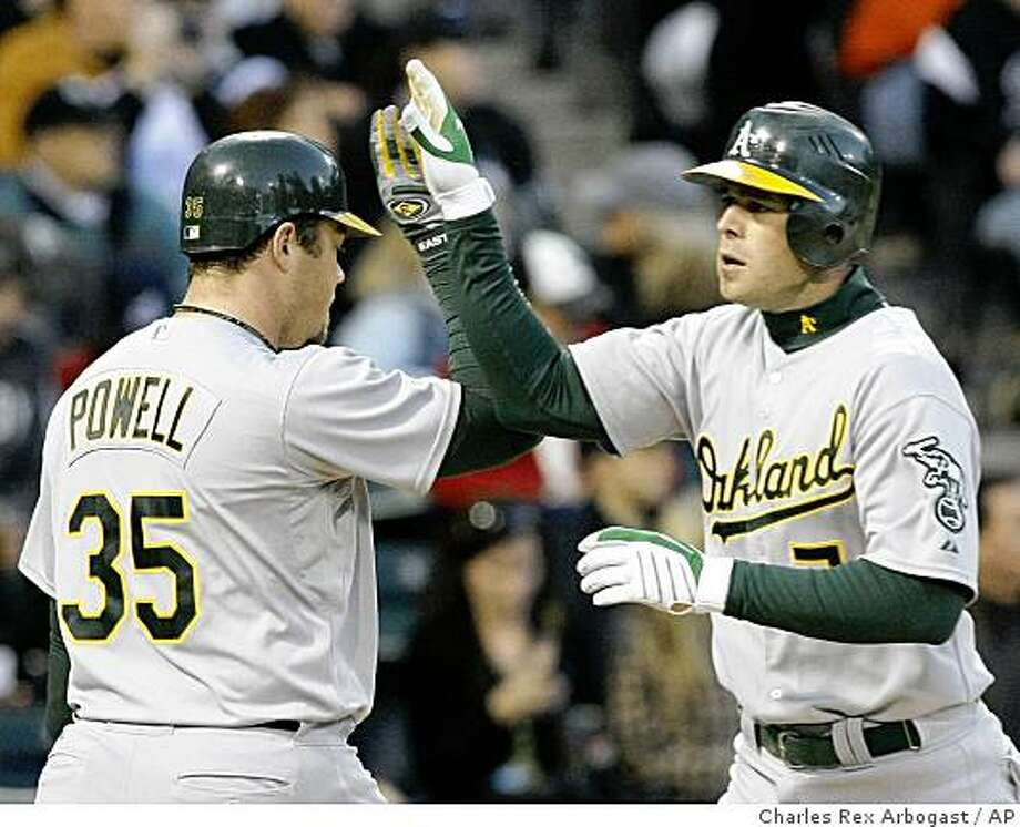 Oakland Athletics' Bobby Crosby, right, is greeted at home plate by Landon Powell after hitting a home run off Chicago White Sox starting pitcher Clayton Richard during the fourth inning of a baseball game Wednesday, June 3, 2009, in Chicago. (AP Photo/Charles Rex Arbogast) Photo: Charles Rex Arbogast, AP