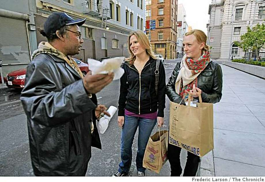 "Gronimo Montoya (left) receives a pair of socks and a dessert from Krista Seiden (middle) and Pauline Karlsen (right) int Stevenson Alley in San Francisco.They are both part of a group called ""A Good Idea"" who walk the city street during in the evening handing out socks and desserts to needy-looking folk on June 4, 2009. Photo: Frederic Larson, The Chronicle"
