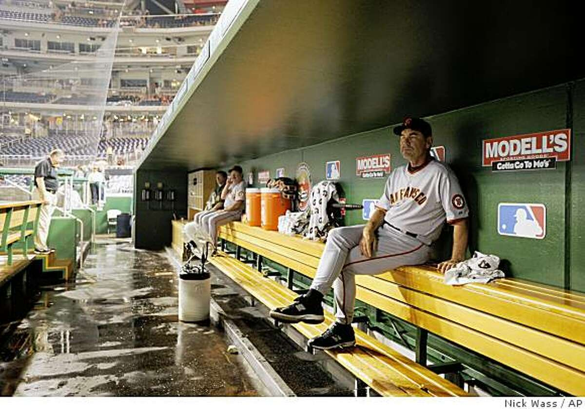 San Francisco Giants manager Bruce Bochy, right, waits out a weather delay in the dugout before a baseball game against the Washington Nationals in Washington, Wednesday, June 3, 2009.
