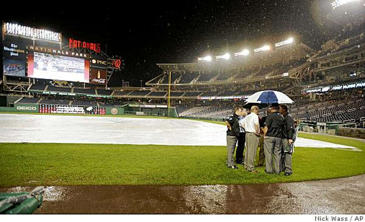 Washington Nationals officials and the umpire crew talk on the field during a rain delay before a baseball game between the Nationals and the San Francisco Giants, Wednesday, June 3, 2009, in Washington. (AP Photo/Nick Wass)