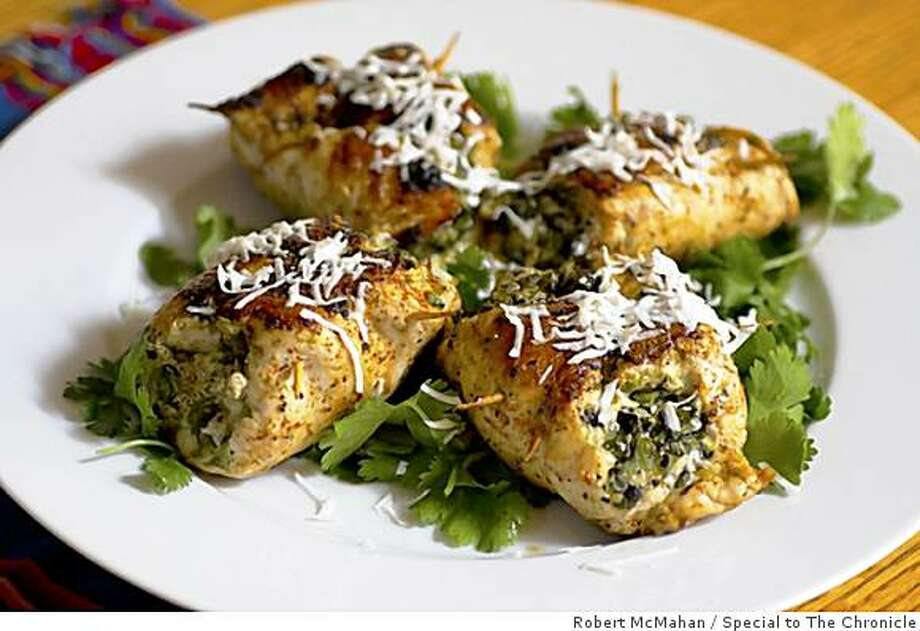 Spread the pesto filling and some cotija cheese over the pounded boneless breasts, top, then roll up and fasten with two toothpicks, above. You can have the finished dish, left, with less than 15 minutes of cooking. Photo: Robert McMahan, Special To The Chronicle