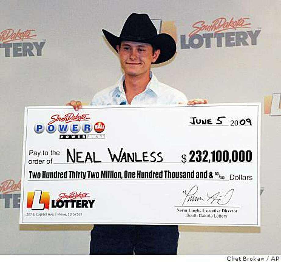 Neal Wanless, 23,  accepts a ceremonial check for winning a $232 million Powerball lottery jackpot, Friday, June 5, 2009, in Pierre, S.D.  Neal Wanless, who lives on his family's 320-acre ranch near Mission, S.D., bought the winning ticket in the nearby town of Winner late last month during a trip to buy livestock feed. He will take home $88.5 million in a lump sum payment after taxes are deducted. (AP Photo/Chet Brokaw) Photo: Chet Brokaw, AP