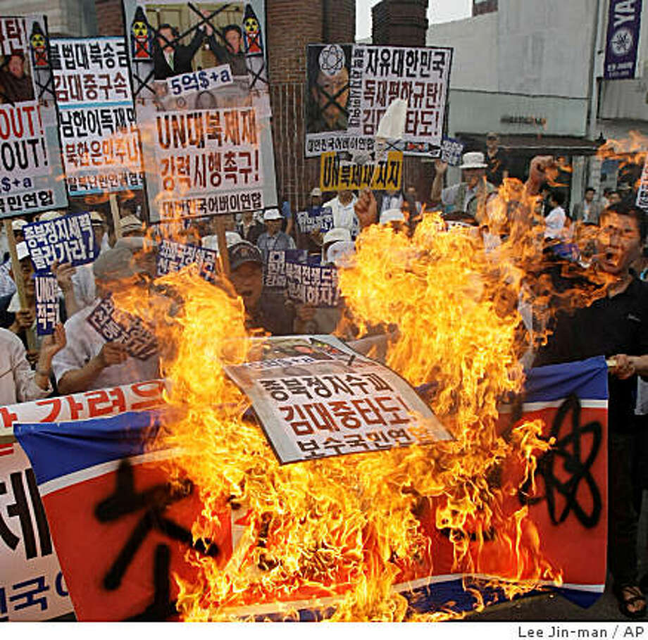 "South Korean protesters burn North Korean national flags during a rally, denouncing the ninth anniversary of the June 2000 summit between former South Korean President Kim Dae-jung and North Korean leader Kim Jong Il in front of Kim Dae-jung's house in Seoul, South Korea, Sunday, June 14, 2009. North Korea's communist regime has warned of a nuclear war on the Korean peninsula while vowing to step up its atomic bomb-making program in defiance of new U.N. sanctions. Banners read: ""Support U.N. sanctions."" (AP Photo/Lee Jin-man) Photo: Lee Jin-man, AP"