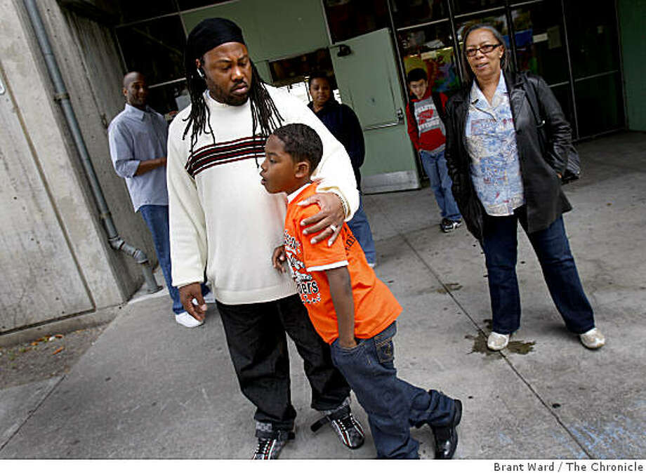 """Cheeko Wells (left) held his son Cheeko Jr. outside the school. Wells belongs to a group called """"Brothers Against Guns"""" and had planned a presentation Monday. entrance as teachers and staff gathered after the shooting. A shooting occurred on the first day of summer school at International Studies Academy Monday June 15, 2009. Photo: Brant Ward, The Chronicle"""