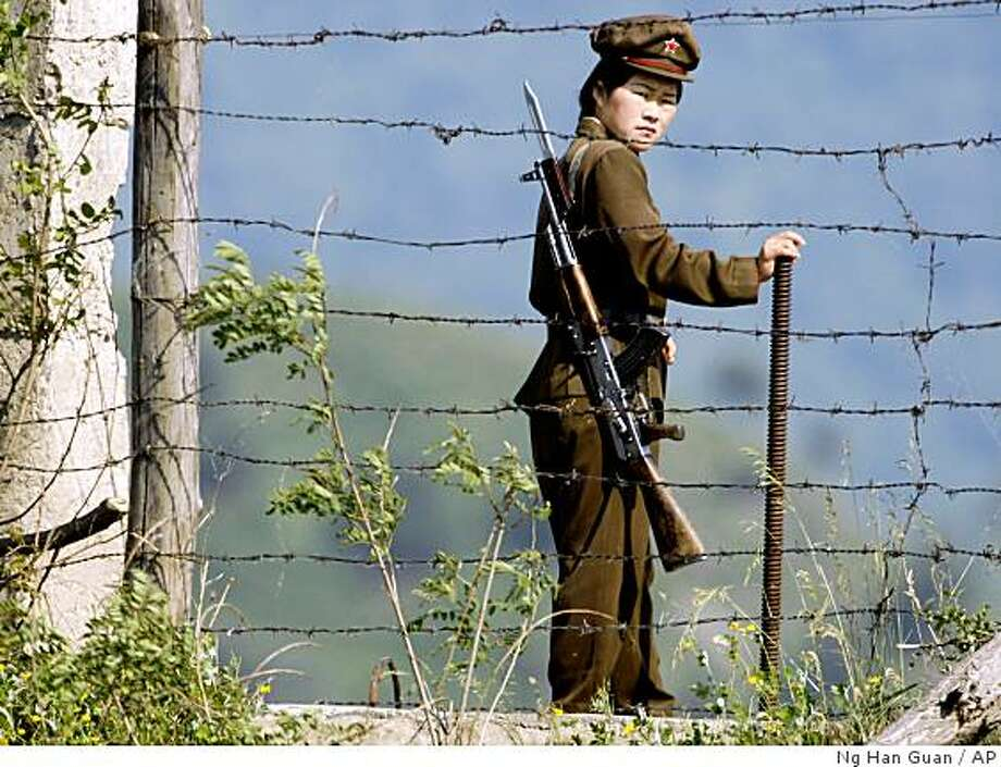 FILE - In this June 3, 2009 file photo, a North Korean soldier stands guard behind a barbed wire fence on the North Korean river bank across from Hekou, northeastern China's Liaoning province.  The widening scope of North Korea's defiance, a rocket launch, a nuclear blast and signs of more long-range and atomic tests to come, suggests there's more to it than the usual brinkmanship. (AP Photo/Ng Han Guan, File) Photo: Ng Han Guan, AP