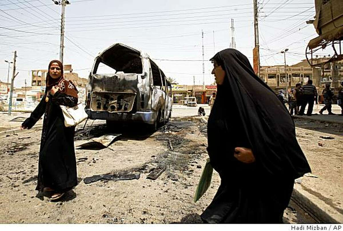 Iraqi women pass by a destroyed minibus after a bomb exploded in the Shaab neighborhood in Baghdad, Iraq, Monday, June 15, 2009. A bomb hidden under a minibus exploded killing two people and wounding nine others, during morning rush hour, police said.