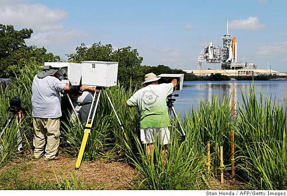 Photographers retrieve their remote cameras after the space shuttle Endeavour launch was delayed due to a leak in the hydrogen vent line during fueling on June 13, 2009 at Kennedy Space Center in Florida. The leak is similar to one that occured in March before the launch of the shuttle Discovery. NASA expects the delay to be a minimum of four days.       AFP PHOTO/Stan HONDA (Photo credit should read STAN HONDA/AFP/Getty Images) Photo: Stan Honda, AFP/Getty Images
