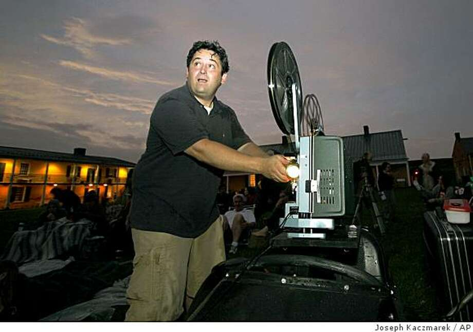 """John Young, creator of West Chester Guerilla Drive-In, prepares the film projector inside Fort Mifflin in Philadelphia on Friday May 29, 2009.  For the last four years or so, the 38-year-old Web developer has been showing 16mm films from a 1970s school projector mounted on the sidecar of his 1977 BMW motorcycle. He's presented more than a dozen movies at locations suited for the theme: """"Meatballs"""" at a canoe rental center, """"Caddyshack"""" on a golf course, and most recently, """"Ghostbusters"""" at Fort Mifflin, a favorite haunt of paranormal investigators. (AP Photo/ Joseph Kaczmarek) Photo: Joseph Kaczmarek, AP"""