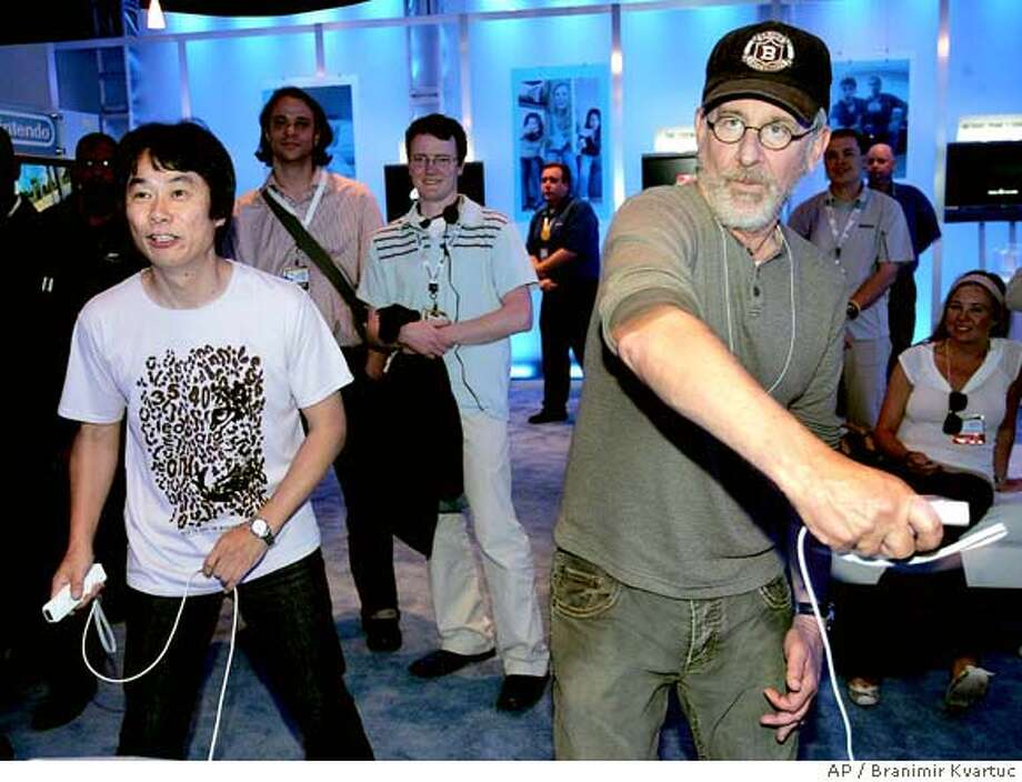 Shigeru Miyamoto, left, legendary video game designer for Nintendo, known as the Spielberg of video games, having created Mario and the Legend of Zelda, plays Tennis with Steven Spielberg on Nintendo's new game console called Wii, using the controller as the racket to physically hit the virtual ball, while attending the E3 Electronic Entertainment Expo in Los Angeles on Friday, May 12, 2006. (AP Photo/Branimir Kvartuc) Photo: BRANIMIR KVARTUC