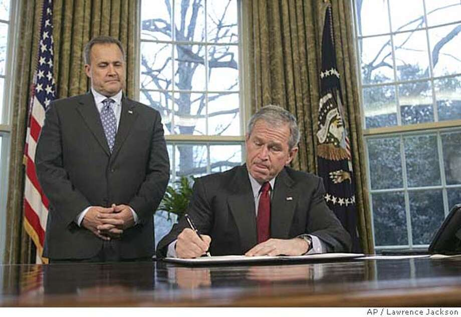 President Bush, accompanied by Budget Director Jim Nussle, signs an executive order protecting American taxpayers from government spending on earmarks, Tuesday, Jan. 29, 2008, in the Oval Office of the White House in Washington. (AP Photo/Lawrence Jackson) Photo: Lawrence Jackson