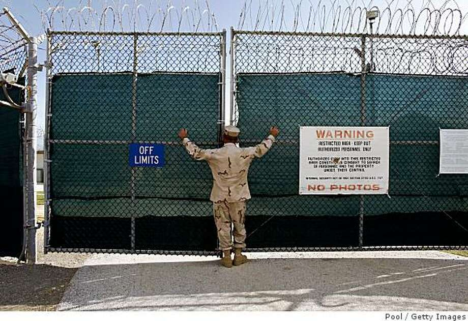 U.S. NAVAL BASE GUANTANAMO, CUBA - JUNE 1:  (EDITORS NOTE: IMAGE REVIEWED BY U.S. MILITARY PRIOR TO TRANSMISSION) A guard stands outside the gate of Camp Iguana detention facility, which houses the Chinese Uighur Guantanamo detainees June 1, 2009 at U.S. Naval Base Guantanamo Bay, Cuba.  Seventeen Uighur detainees at Guantanamo are cleared for release but continue to be held because China considers them terrorists and has indicated they will be incarcerated if they return.  (Photo by Brennan Linsley-Pool/Getty Images) Photo: Pool, Getty Images