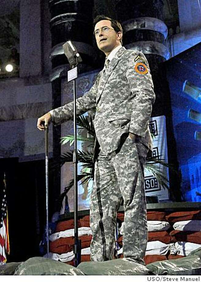 "Stephen Colbert wears a custom-made suit by Brooks Brothers for the taping of ""Operation Iraqui Stephen: Going Commando."" The American clothier designed the one-of-a-kind, made-to-measure camouflage suit in Army ?digicamo? material based on the ?Madison? style suit from the company?s 1818 Collection. The suit has all of the finish details found in Brooks Brothers suiting, including a tan lining with the jacket sleeves lined in a cream and green striped fabric. The garment is finished with a Brooks Brothers tag reading ?Custom Tailored.?Actor/comedian Stephen Colbert (left) of Comedy Central's ""The Colbert Report"" performs for U.S. military personnel at Al Faw Palace in Baghdad, Sunday, June 7, 2009.  Colbert is participating in a USO/Armed Forces Entertainment tour to the Persian Gulf region June 5-11, 2009. (USO Photo by Steve Manuel) Photo: USO/Steve Manuel"