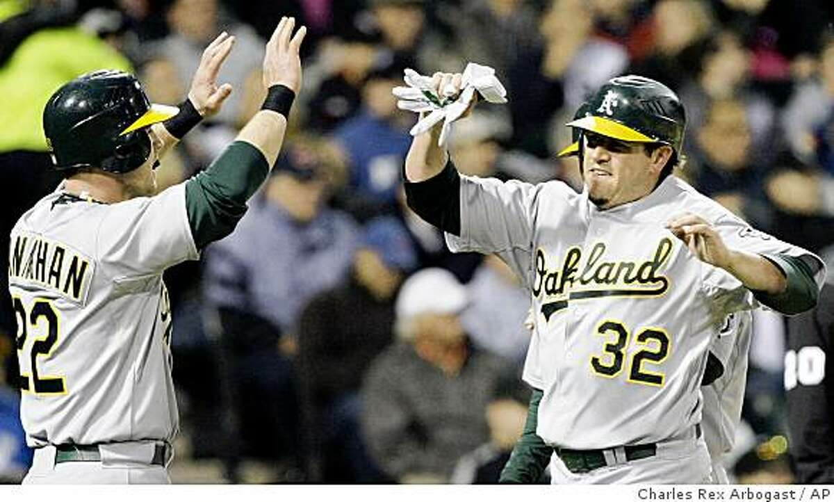 Oakland Athletics' Jack Hannahan, left, and Jack Cust celebrate after they both scored off a double by Matt Holliday during the fifth inning of a baseball game against the Chicago White Sox in Chicago, Tuesday, June 2, 2009. (AP Photo/Charles Rex Arbogast)