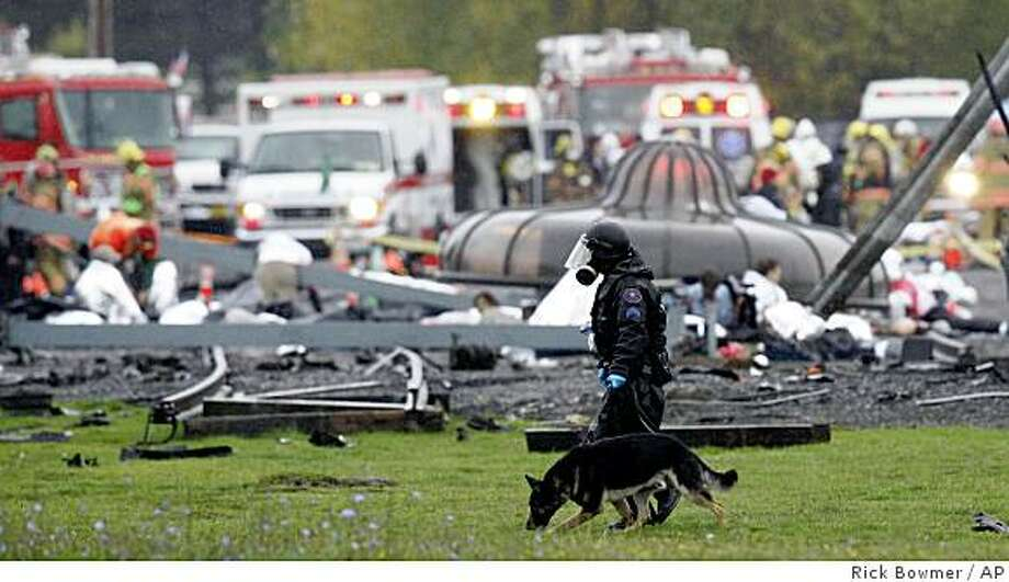 "**ADVANCE FOR SUNDAY, JUNE 14** FILE - In this Oct. 16, 2007 file photo, a responder using a dog patrols the grounds following a simulated radioactive ""dirty bomb"" attack, which the U.S. Department of Homeland Security calls it one of the largest civilian exercises ever conducted, in Portland, Ore.   (AP Photo/Rick Bowmer, file) Photo: Rick Bowmer, AP"