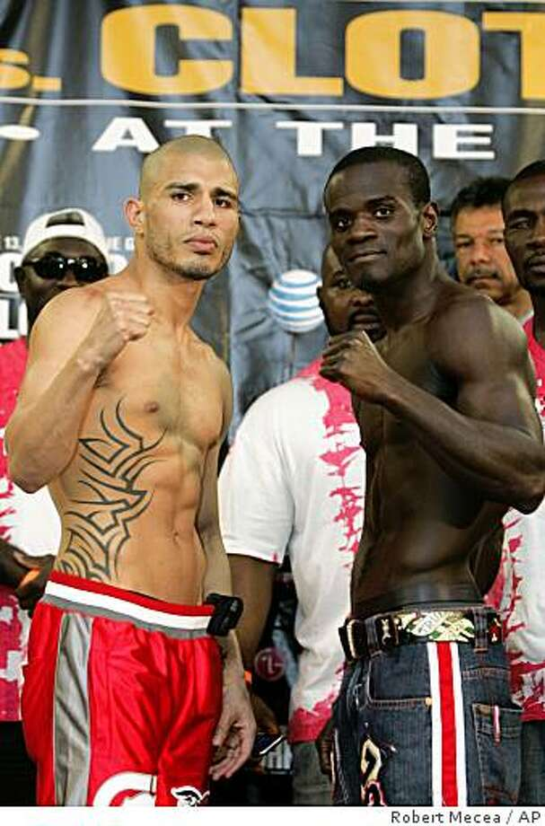Welterweights Miguel Cotto, left, and Joshua Clottey pose with their fists up after their weigh-in at Madison Square Garden, in New York, Friday, June 12, 2009.  Cotto will be fighting Clottey in Madison Square Garden, Saturday, June 13, 2009.    (AP Photo/Robert Mecea) Photo: Robert Mecea, AP