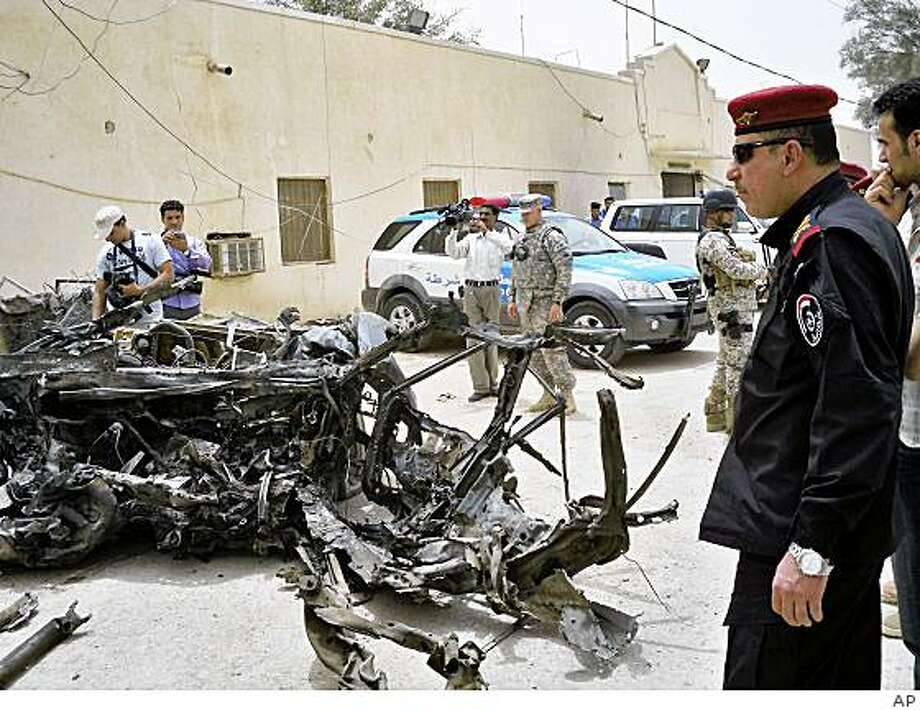 In this image released by the US Army, Provincial Director of Police for Dhi Qar province Maj. Gen. Sabah Al-Fatlawi, looks at the damage caused by a car bomb in the town of Bathaa, which is near Nasiriyah, about 200 miles (320 kilometers) southeast of Baghdad, Iraq, Wednesday, June 10, 2009. A car bomb ripped through a market in southern Iraq's Shiite heartland Wednesday as shoppers were buying meat and vegetables, killing and wounding dozens, officials said. (AP Photo/US Army) Photo: AP
