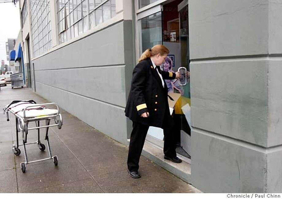 With a medical examiner's gurney standing by, left, Fire Chief Joanne Hayes-White shuts the door of a print shop where a female employee reportedly died while operating printing press equipment in San Francisco, Calif. on Tuesday, Jan. 29, 2008. It's the second industrial accident fatality in two days in the city. MANDATORY CREDIT FOR PHOTOGRAPHER AND S.F. CHRONICLE/NO SALES - MAGS OUT Photo: PAUL CHINN