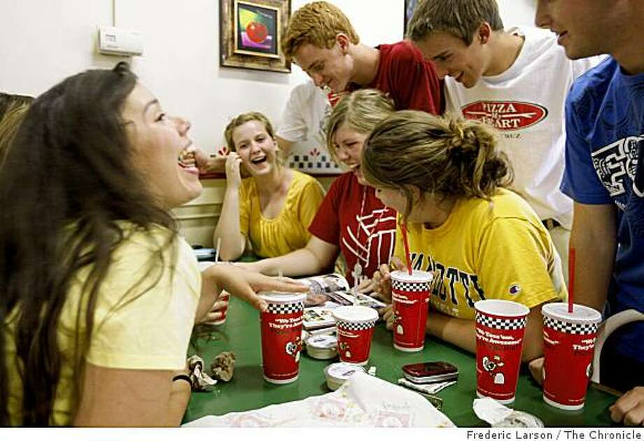 Katie Schultz (center in front of book) pages through the Rio Vista High school 2009 yearbook as her classmates huddle around her while eating pizza after school at the Pizza Factory on Main Street in Rio Vista on May 29, 2009 Photo: Frederic Larson, The Chronicle