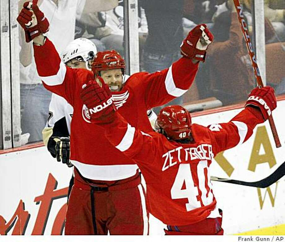 Detroit Red Wings' Johan Franzen, from Sweden, celebrates with teammate Henrik Zetterberg, from Sweden, after scoring a goal as  Pittsburgh Penguins' Sidney Crosby skates by during the second period of Game 1 of the NHL Stanley Cup finals hockey series in Detroit, Saturday, May 30, 2009. (AP Photo/The Canadian Press, Frank Gunn) Photo: Frank Gunn, AP