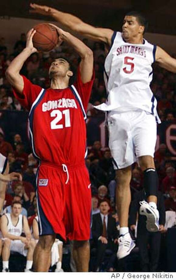 Gonzaga's Robert Sacre, center, shoots as St. Mary's Yusef Smith, right, guards during the first half of a college basketball game, Monday, Feb. 4, 2008 in Moraga, Calif. (AP Photo/George Nikitin) Photo: George Nikitin