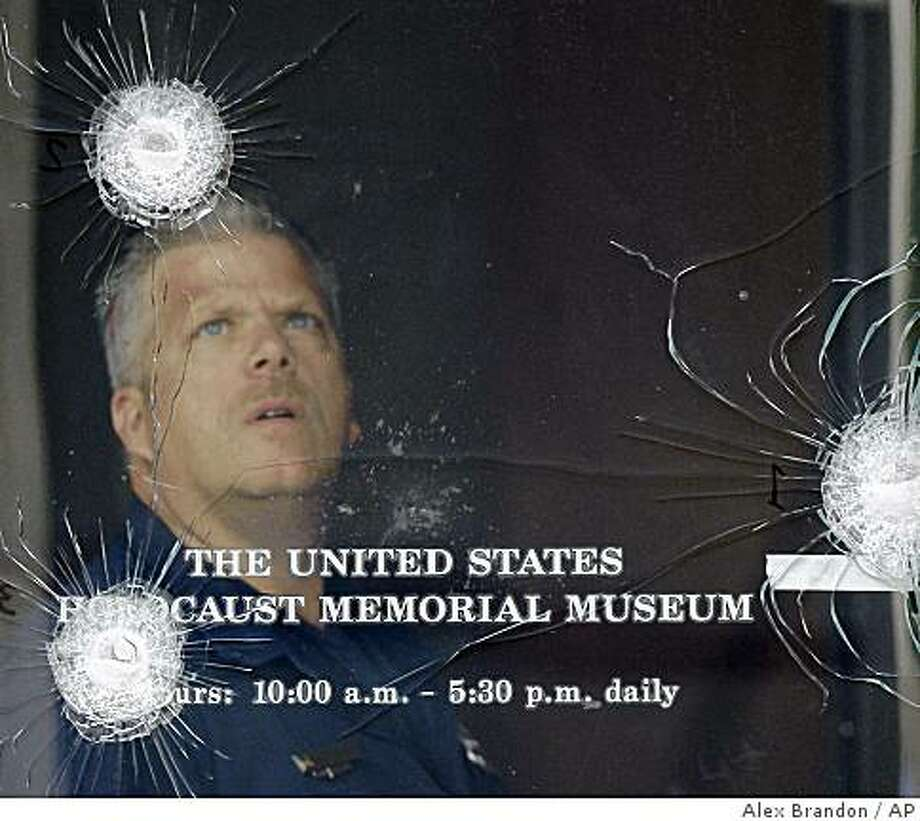 Washington police investigator George Klein Jr. examines bullet strikes in one of the doors of the U.S. Holocaust Memorial Museum in Washington, Thursday, June 11, 2009, a day after a shooting left a security officer dead and the gunman wounded. (AP Photo/Alex Brandon) Photo: Alex Brandon, AP