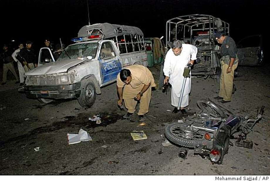 Pakistani police officer collect evidence after a blast at a check point on the outskirt of Peshawar, Pakistan, Thursday, June 11, 2009.  Police in Pakistan say assailants attacked a checkpoint using a grenade.  When more police rushed to the scene a suicide bomber ran forward and blew himself up police said. Photo: Mohammad Sajjad, AP
