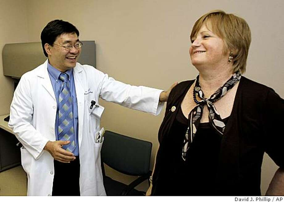 n this Wednesday May 27, 2009 photo, Dr. Patrick Hwu, left, talks with his cancer patient Hilde Stapleton during an examination at The University of Texas MD Anderson Cancer Center  in Houston. Stapleton has been receiving an experimental treatment for melanoma. (AP Photo/David J. Phillip) Photo: David J. Phillip, AP