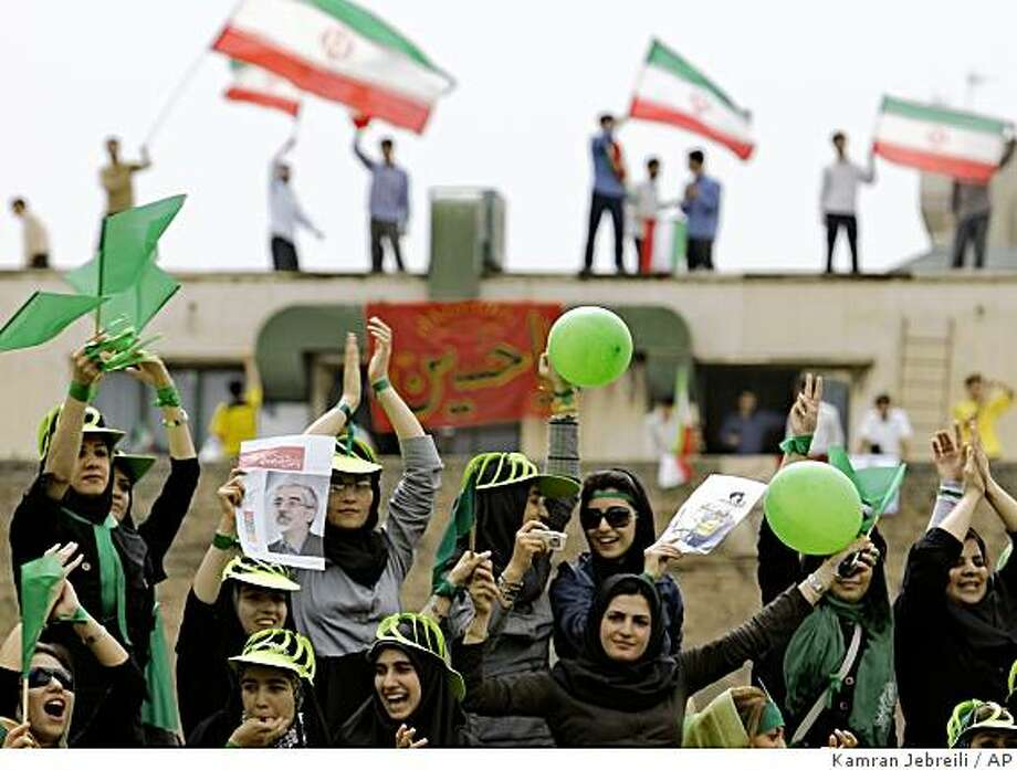 Women supporters of reformist candidate,  Mir Hossein Mousavi chant pro reform slogans at the Heidarnia stadium as the supporters of hard line President Mahmoud Ahmadinejad wave Iranian flag in the background  in the final days of the election race in Tehran, Tuesday, June 9, 2009. (AP Photo/Kamran Jebreili) Photo: Kamran Jebreili, AP