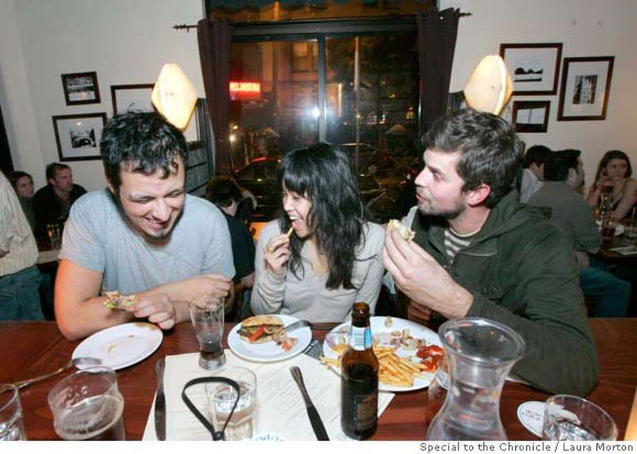 Maximiliano Villicana, Tracy Ong and Jacob Ruch (left to right) share a few bites on a Saturday night at Monk's Kettle, a high end beer bar in the Mission District that also serves food. (Laura Morton/Special to the Chronicle) Photo: Laura Morton