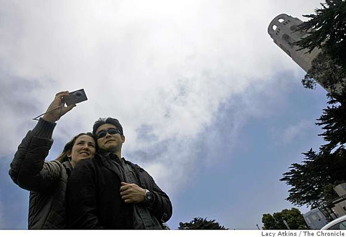 Freni Waidelich and Hirofumi Kamei from Victoria, BC take pictures of the city over the large juniper trees at Coit Tower, Thursday May 28, 2009, in San Francisco, Calif.