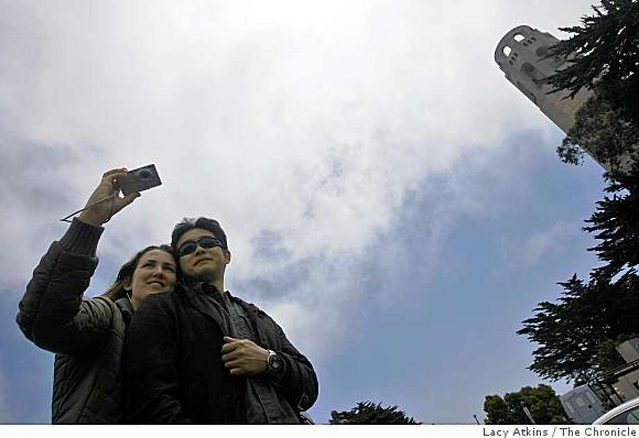 Freni Waidelich and Hirofumi Kamei from Victoria, BC take pictures of the city over the large juniper trees at Coit Tower,  Thursday May 28, 2009,  in San Francisco, Calif. Photo: Lacy Atkins, The Chronicle