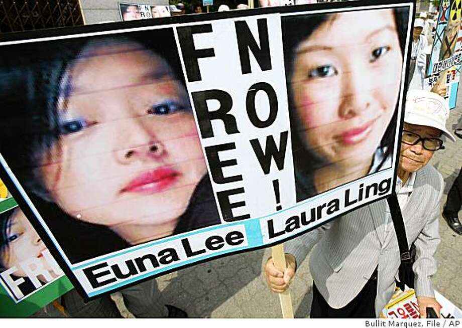"FILE-In this file photo taken on Thursday, June 4, 2009, a South Korean protester displays portraits of American journalists detained in North Korea as they shout slogans during a rally at a public park in Seoul.  North Korea's state news agency says the country's top court has convicted the two U.S. journalists and sentenced them to 12 years in labor prison.    The Korean Central News Agency says the Central Court tried American journalists Laura Ling, right photo,  and Euna Lee, left photo,  from June 4 to 8.  It said Monday, June 8, 2009,  the trial confirmed an unspecified ""grave crime"" against the nation, and of illegally crossing into North Korea.   (AP Photo/Bullit Marquez, File) Photo: Bullit Marquez, File, AP"