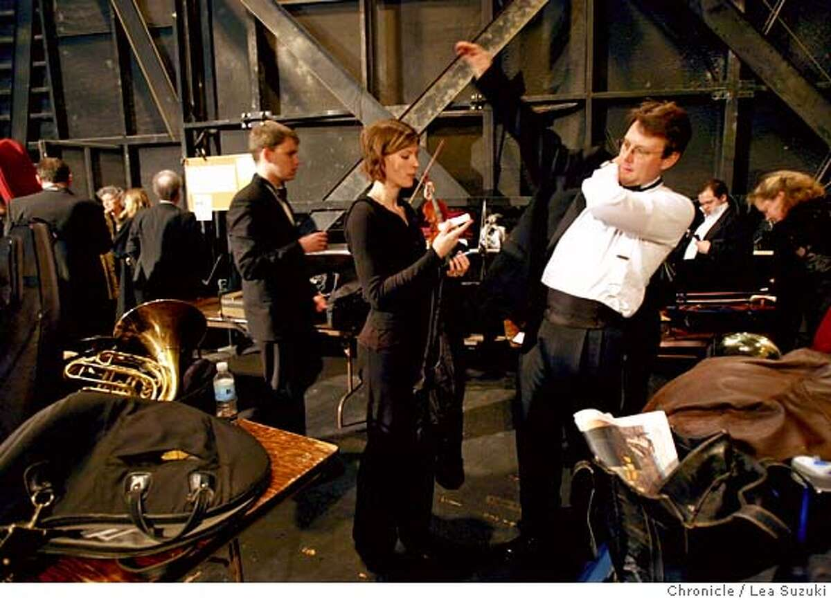 From right; Trombonist Bruce Chrisp puts on his jacket while his wife Meredith Brown, who plays the French Horn, talks with him before their perforrmance with the Marin Symphony. Both appear in the movie