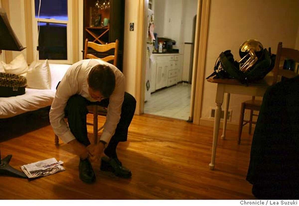 Trombonist Bruce Chrisp ties his shoes as he dresses before leaving for his gig at the Marin Symphony in San Rafael. He appears in the movie