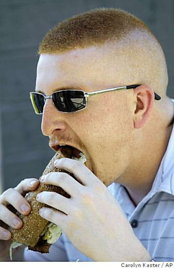 In this photo taken May 21, 2009, Wes Hoover of Mechanicsburg, Pa., bites into his roast beef sub at Quiznos in Mechanicsburg, Pa. Whether sit-down or take-out, restaurant chains are finding the key to persuading people to spring for lunch these days is keeping the tab below $10. (AP Photo/Carolyn Kaster) Photo: Carolyn Kaster, AP