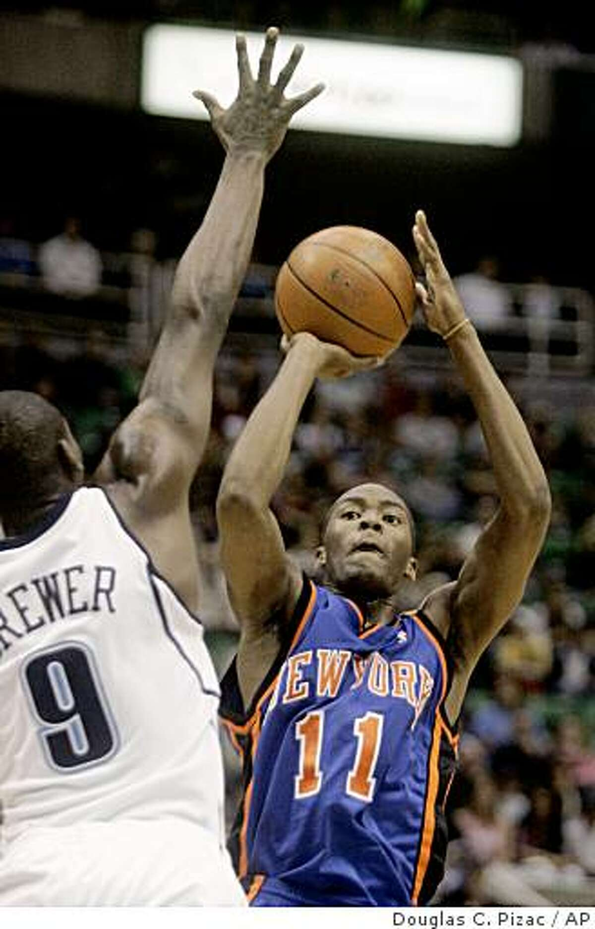 New York Knicks guard Jamal Crawford (11) shoots against Utah Jazz guard Ronnie Brewer (9) during the first quarter of the NBA basketball game Wednesday, Jan. 30, 2008, in Salt Lake City. Crawford finished the night with 26 points for the game-high and 9 assists. (AP Photo/Douglas C. Pizac)