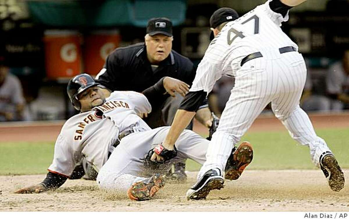 Florida Marlins' Ricky Nolasco (47) tags out San Francisco Giants' Pablo Sandoval, left, at home plate in the fourth inning of a baseball game as home plate umpire Brian O'Nora watches on Sunday, June 7, 2009, in Miami. (AP Photo/Alan Diaz)