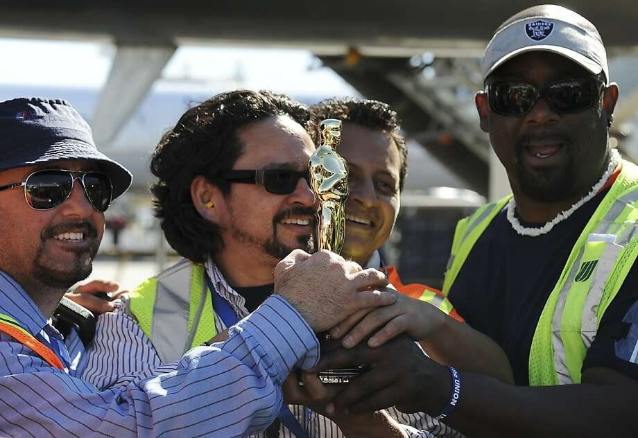 United Airlines ramp service employee Julio Cesar Mora (2L) and coworkers hold up an Oscar statuette after a flight from Chicago arrived with a shipment of 42 Oscar statuettes, at Los Angeles International Airport February 9, 2012.  The 84th annual Academy Awards will be presented in Hollywood, California on February 26th.  AFP PHOTO / Robyn Beck (Photo credit should read ROBYN BECK/AFP/Getty Images) Photo: Robyn Beck, AFP/Getty Images